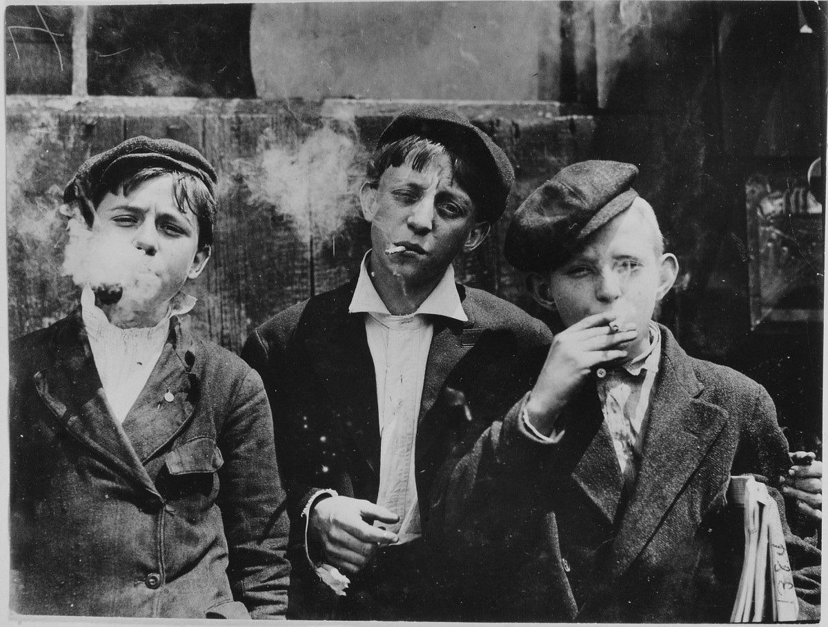 Lewis Wickes Hine - 11:00 A. M . Monday, May 9th, 1910. Newsies at Skeeter's Branch, Jefferson near Franklin. They were all smoking. Location: St. Louis, Missouri. (1910)
